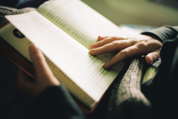 close-up of a woman reading a book, with soft indoor light hitting her hands holding the open book.