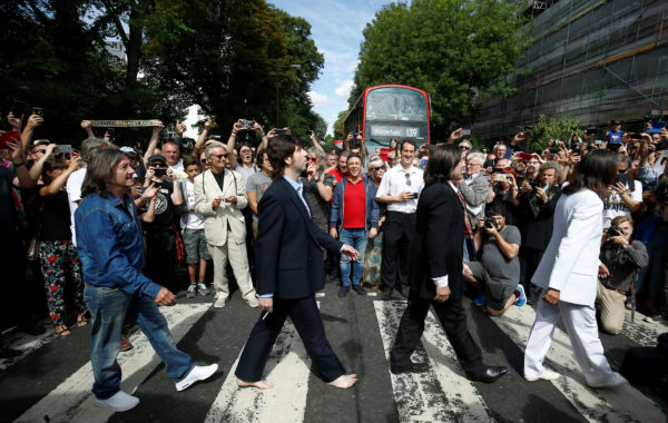 People take pictures as the Beatles cover band members walk on the zebra crossing on Abbey Road in London, Britain August 8, 2019. Photo by REUTERS/Henry Nicholls