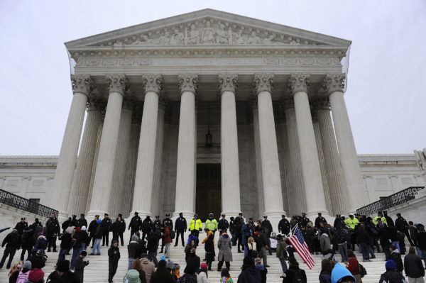 Police form a line after arresting demonstrators on the steps of the U.S. Supreme Court building, on the 2012 anniversary of the Citizens United decision, in Washington. Under the banner 'Occupy the Courts,' organizers expect thousands of people to rally on Friday at 150 courthouses to mark the second anniversary of the Supreme Court ruling that protesters say allows unlimited corporate campaign donations. Photos By Jonathan Ernst via Reuters.