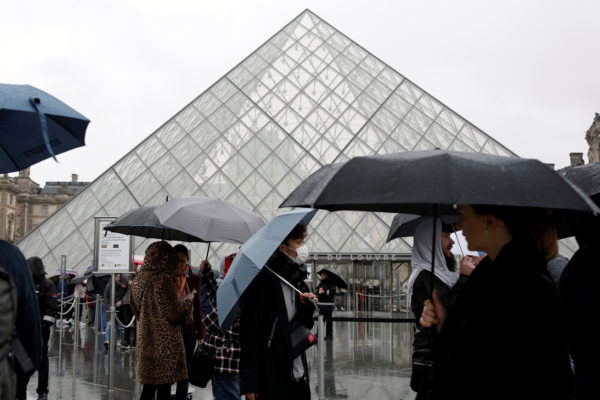 A tourist wearing a mask walks away from the Louvre as the staff closed the museum during a staff meeting about the coronavirus outbreak, in Paris, France. Photo by Benoit Tessier/Reuters