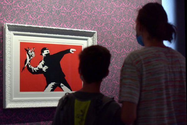 ROME, ITALY - SEPTEMBER 11: People, wearing face masks, visit the exhibition 'Banksy: A visual Protest' on September 11, 2020 in Rome, Italy. The exhibition, containing over 90 works, within the 16th-century architecture of the Chiostro del Bramante in Rome will run until April 11. (Photo by Simona Granati - Corbis/Corbis via Getty Images)